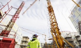 construction site and geodetist, cranes and scaffoldings