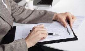 Hand einer Geschäftsfrau am Schreibtisch mit Stift und Klemmbrett