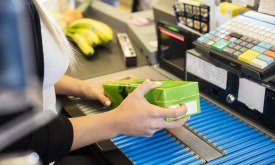 Cropped image of female cashier scanning juice pack's barcode in supermarket