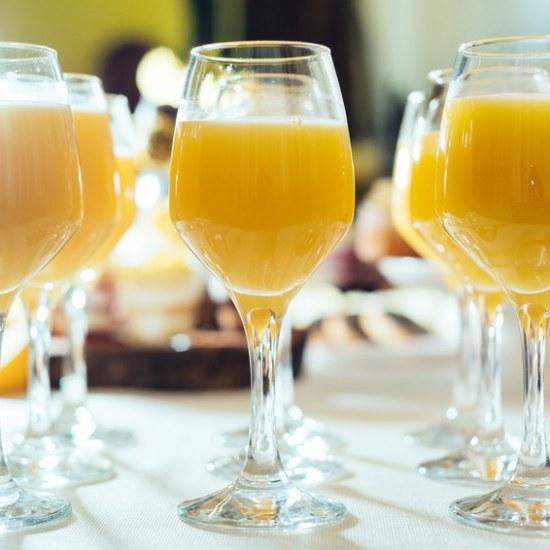 Glasses with tasty fresh orange fruit juice on summer wedding greeting